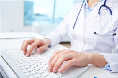 photo of nurse typing on computer
